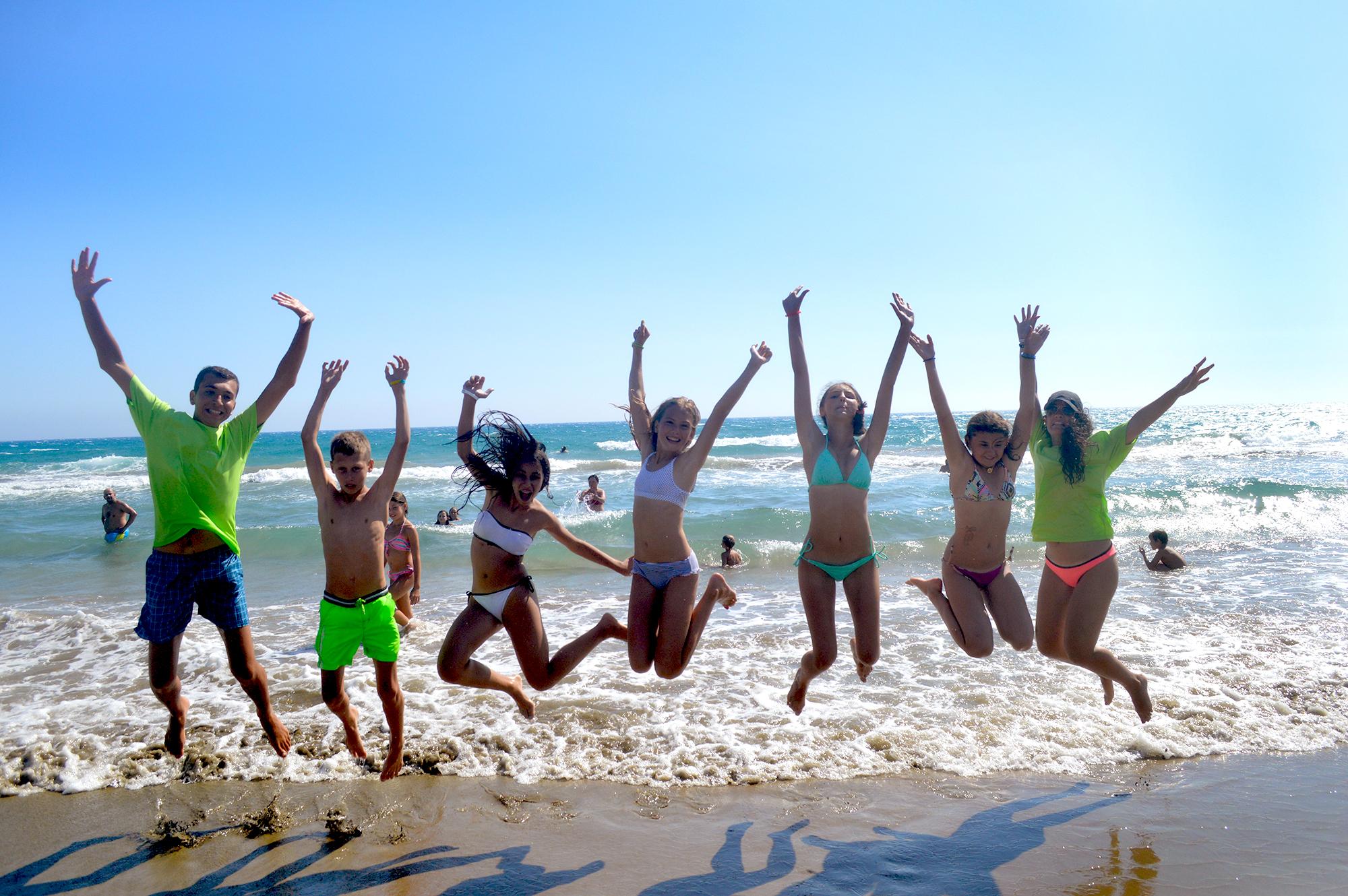 Дети в купальниках на пляже прыгают вверх