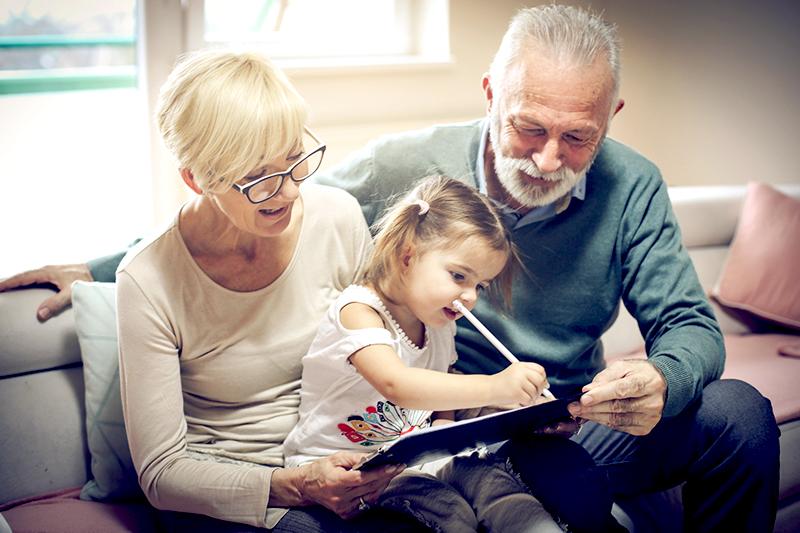 Дедушка и бабушка помогают внучке учить иностранный язык