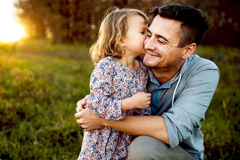 Дочка целует папу во время совместного отдыха