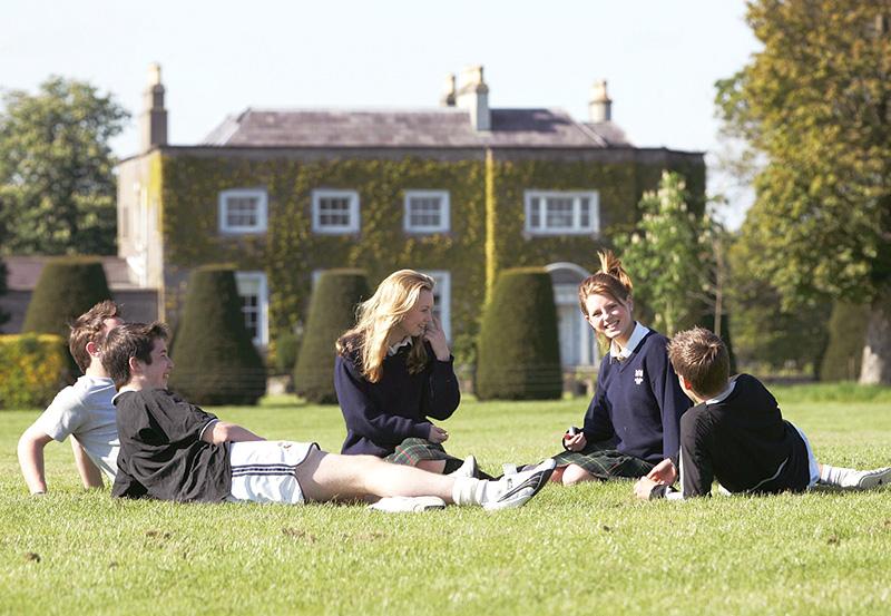 Девочки и мальчики в школьной форме сидят на траве перед зданием школы