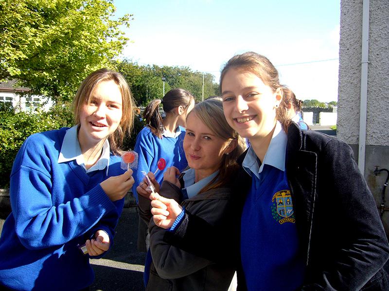 Три девочки в школьной форме едят леденцы на палочке