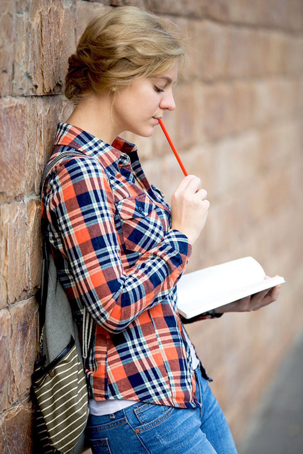 Девочка читает книгу, опираясь на дерево