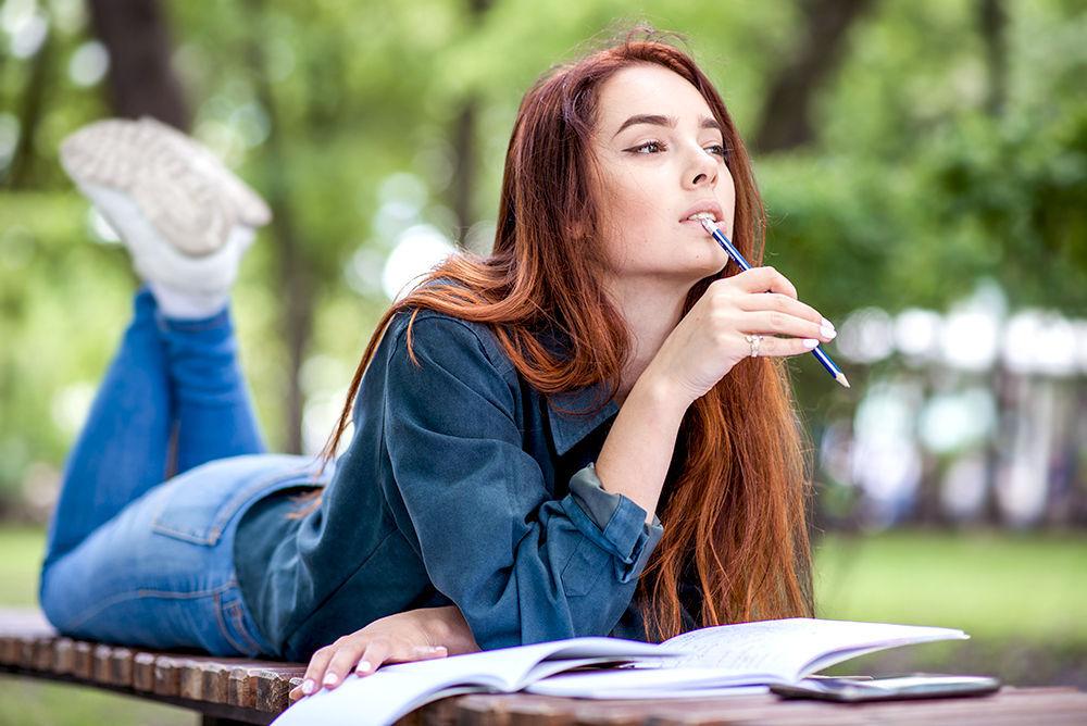 девочка учится и грызет карандаш