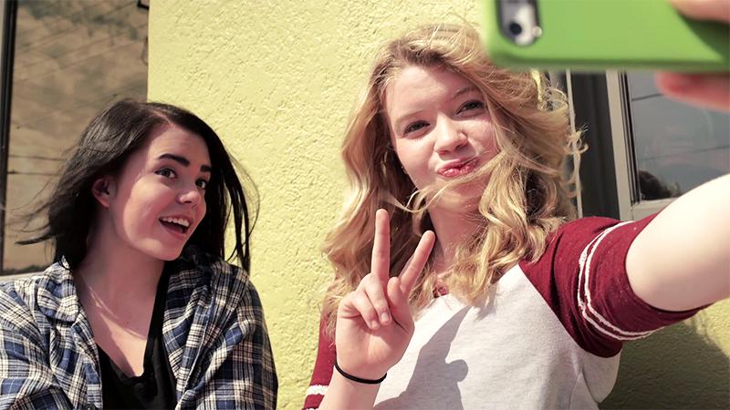Две девочки делают селфи на фоне школы в Америке