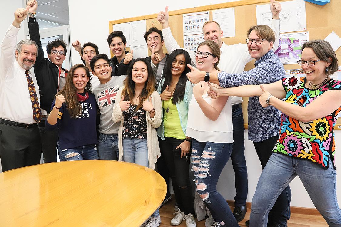 Студенты в Германии улыбаются и поднимают пальцы вверх