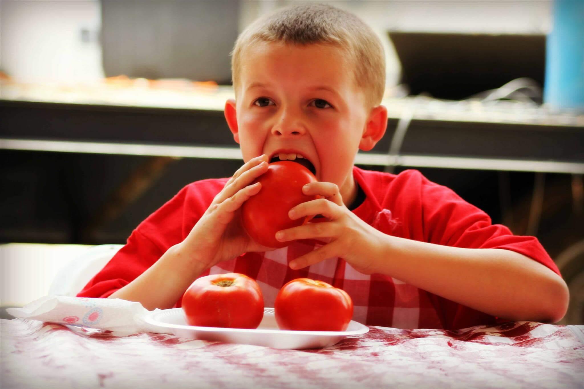 Мальчик кушает помидор