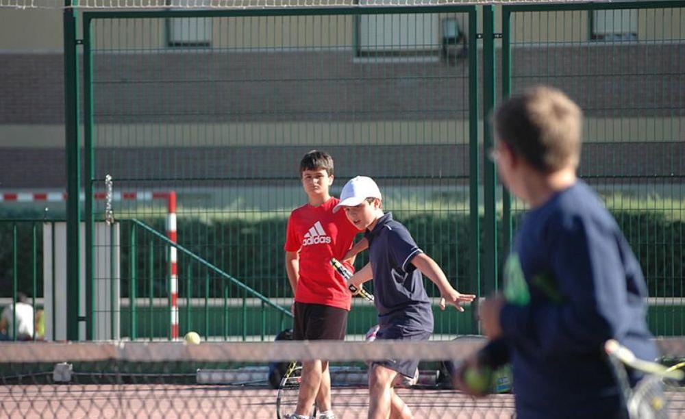 дети играют в теннис в лагере King's College, The British School of Madrid