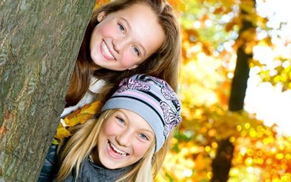 две девочки выглядывают из-за дерева