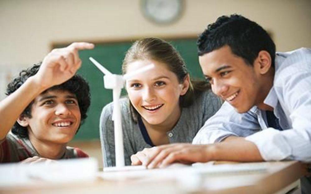Два мальчика и девочка смотрят на модель ветряка
